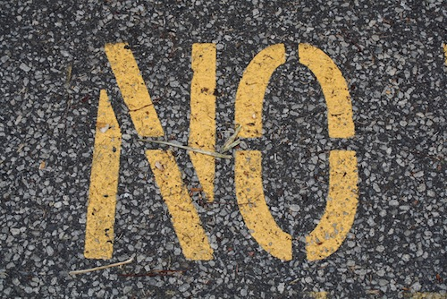 "Spray painting of the word ""No""."