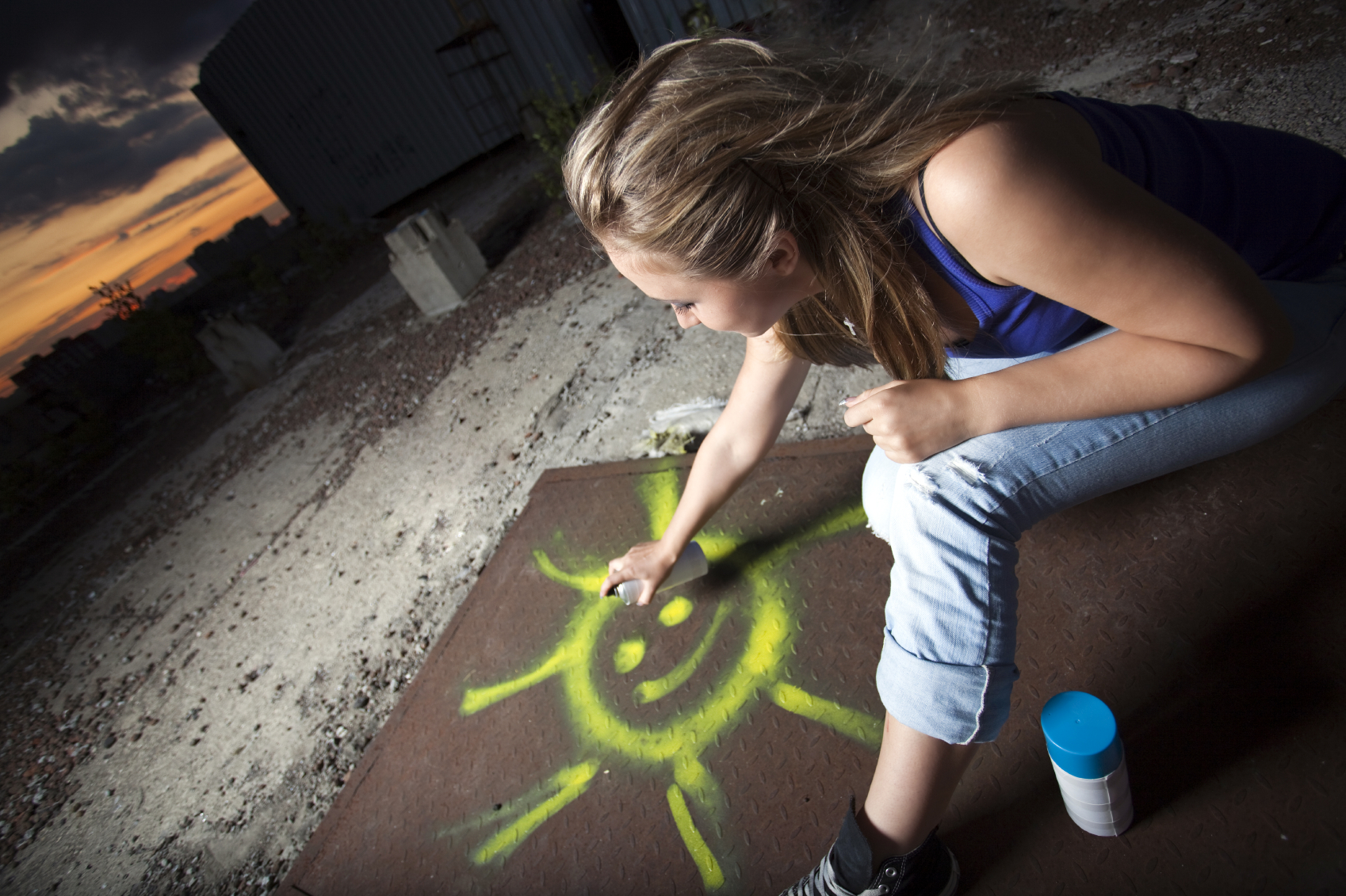 Woman spray painting an image of a happy sun